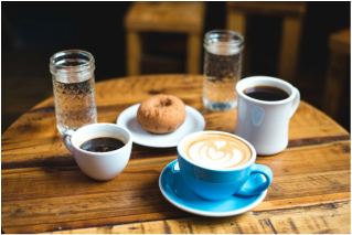 Coffee cups, water glasses and a doughnut on a rustic table