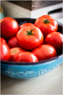 Ripe red tomatoes in a blue bowl