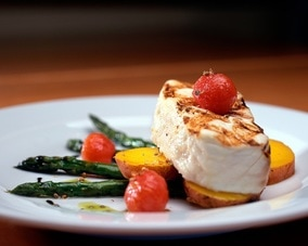 Lovely piece of grilled fish on asparagus, potatoes and tomatoes